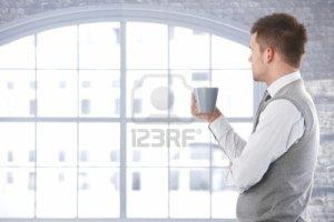 9538176-casual-hombre-mirando-por-la-ventana-pensando-beber-te